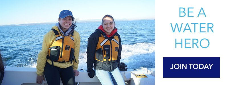 Two volunteers smile at the camera on boat patrol. They are sitting on the deck of the boat with water behind them.